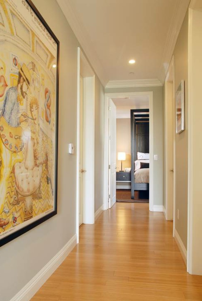 warm pale orange laminate floor, inside a corridor with pale grey walls, and white doors, large framed artwork on one wall