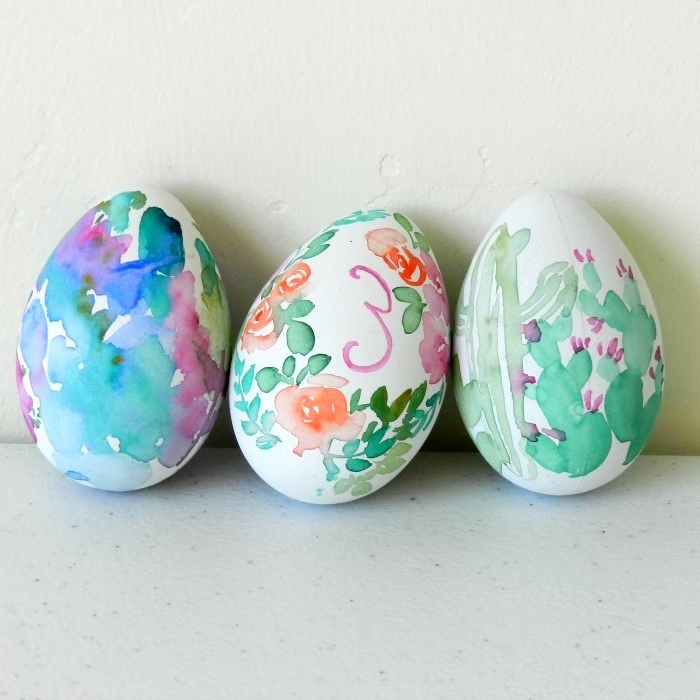 cacti and roses, painted on white eggs with watercolors, easter egg designs, letters and other shapes are also visible on the eggs