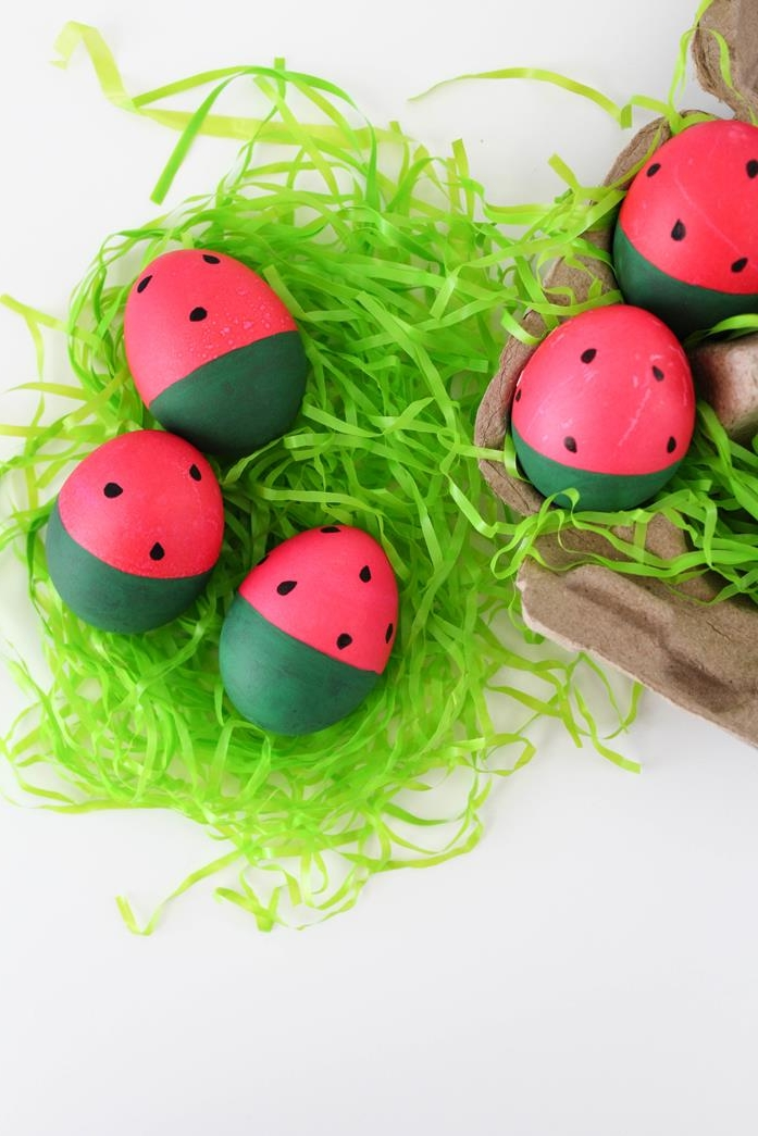 hot pink and dark green easter eggs, painted to look like watermelon slices, easter egg ideas, placed on green easter grass