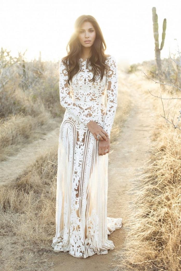 cutout white lace wedding dress, boho fashion gown, worn by brunette woman, with long wavy hair, standing on a desert road