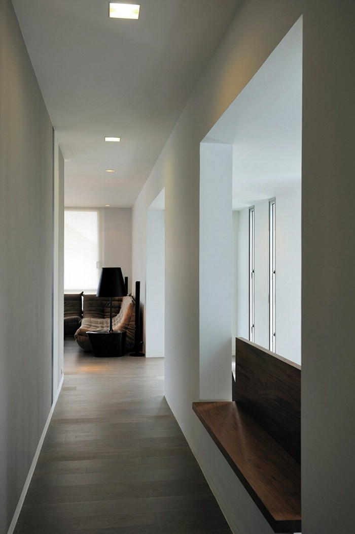 white corridor with windows on one side, minimalist wooden bench, laminate floors and square ceiling lamps, hallway decor ideas, furniture in background