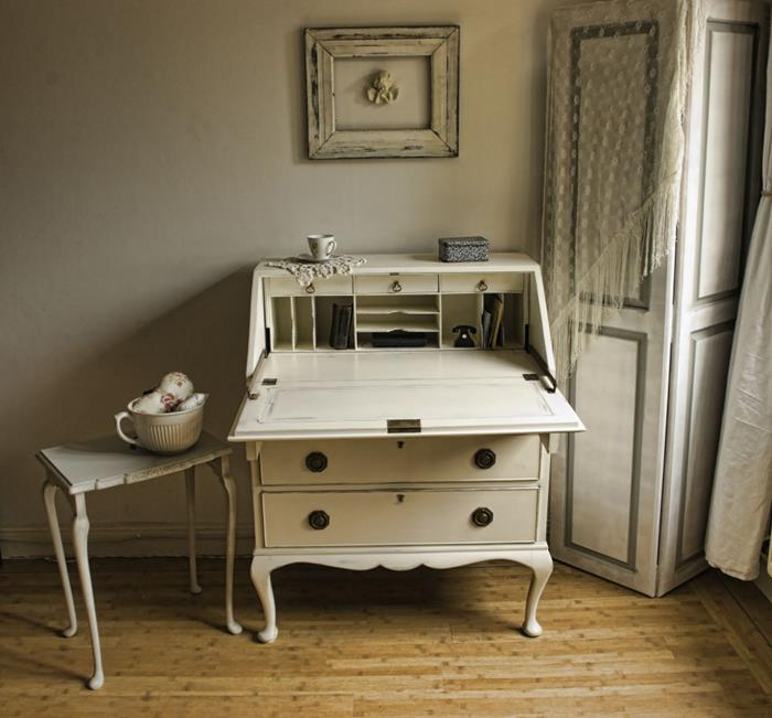 country chic décor, off-white antique cupboard-turned-writing-desk, with black handles, near small ornate table, screen and empty decorative frame