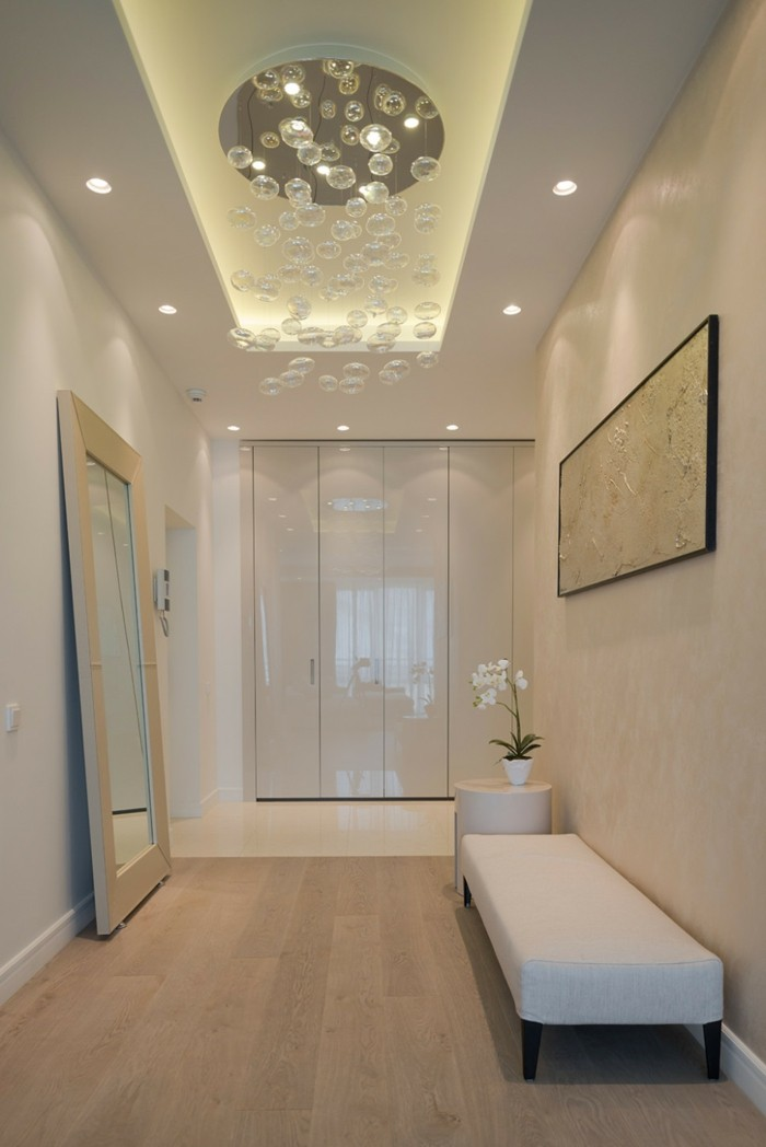 hallway decor, bright room with pale wooden floor, light cream walls, mirror in white frame, white settee and matching table, ceiling lamp with many crystal orbs, white framed painting