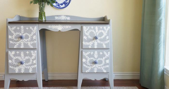 clear glass flower vase, on grey desk with drawers, hand-decorated with white patterns, near window with teal curtain