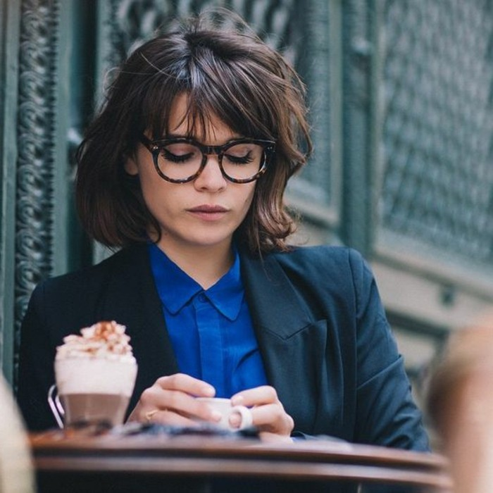 brunette hairstyles, woman wearing blue shirt, dark blue-green blazer, and glasses, with messy wavy bob and bangs, holding small white coffee cup