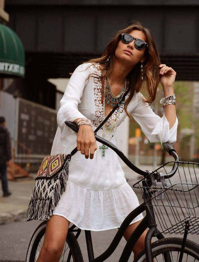 boho style, brunette woman with sunglasses, in embroidered white mini dress, with jewelry and a tasseled tribal crossbody bag, sitting on a bike
