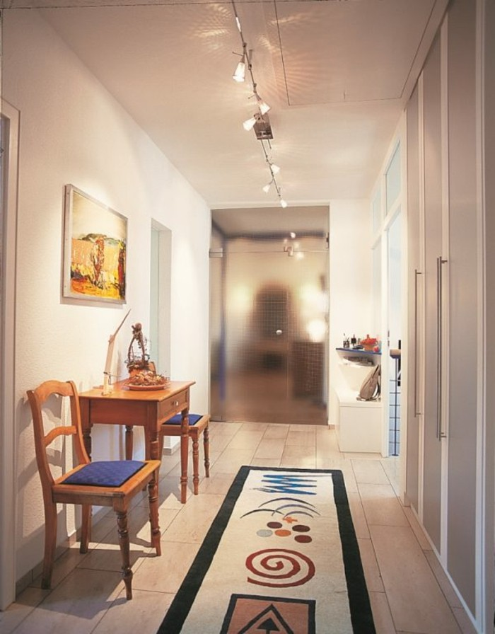 rug in beige and black, with several abstract shapes in different colors, long hallway runners, inside a hall with white walls, containing small wooden table and two chairs