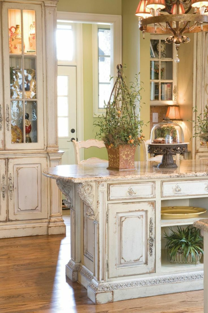 indoor plants and various decorations, inside a shabby chic kitchen, with vintage chandelier, and worn-looking antique furniture, with chipped white paint