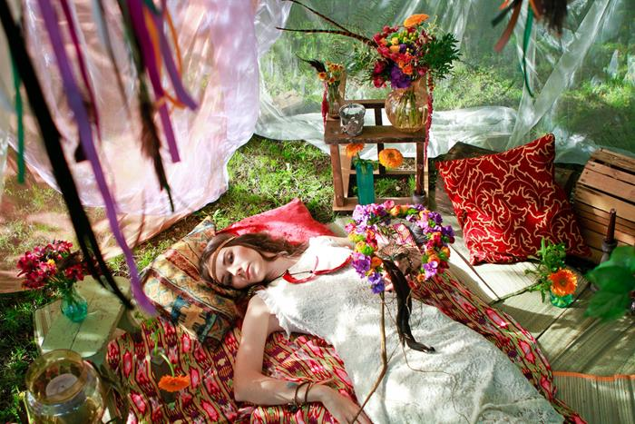 woman in long dress, made of white lace, lying on multicolored boho style, blanket, surrounded by cushions, flowers and ornaments