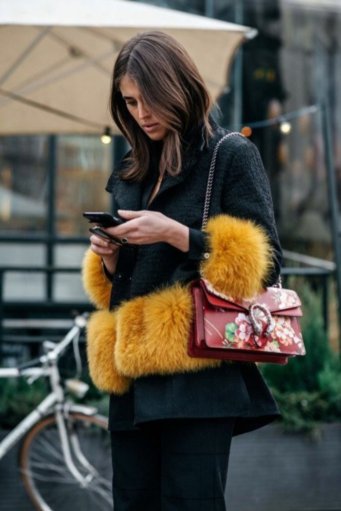 serious looking young woman, dressed in a dark green textured coat, with yellow fur trims, with dark trousers and a red bag, brunette hairstyles, shoulder length wavy hair
