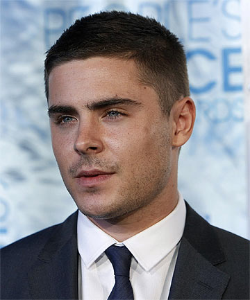 ceasar classic hairstyle, with slight fade, short guy haircuts, worn by zac effron, in black suit, with white shirt and navy tie