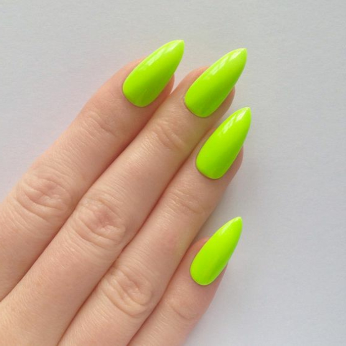 four slender fingers, with long and sharp pointy nails, painted in bright acid green, greenish-yellow color, bright and unusual