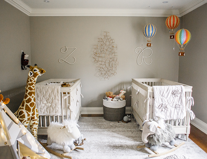 rocking gray elephant, and fluffy white horse, large stuffed giraffe toy, two white cribs, floating air balloon decorations, in room with gray walls, twin nursery ideas
