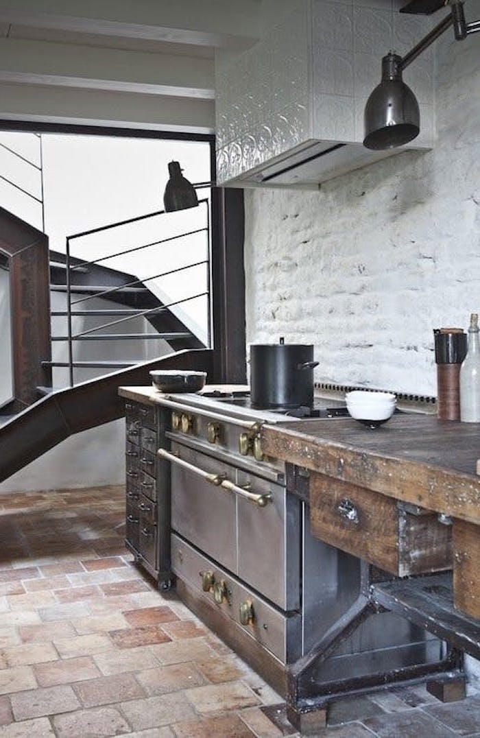 worn wooden cupboard, near black antique stove, with a vintage cooking pot, beige stone tiled floor, brick wall painted white