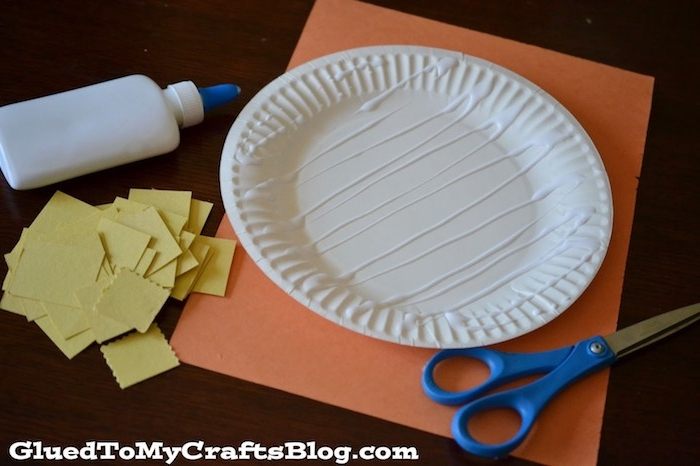glue spread on round paper plate, resting on sheet of orange card, easter crafts for preschoolers, near blue scissors, glue bottle and many pieces of yellow paper