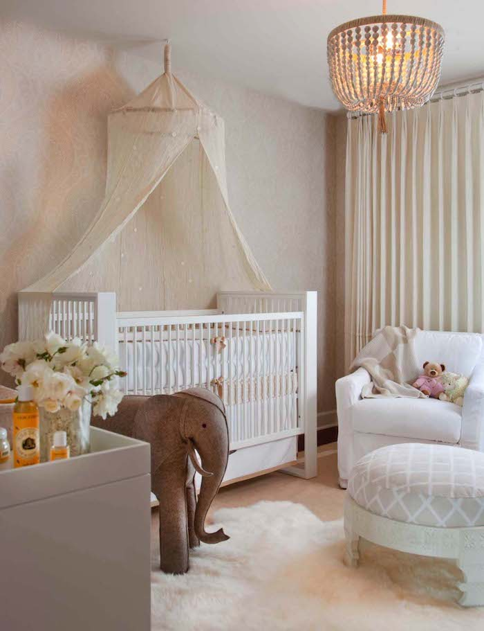 sparkly ivory baldachin, over white classical crib, near large elephant toy, made from brown fabric, girl nursery themes, white armchair nearby