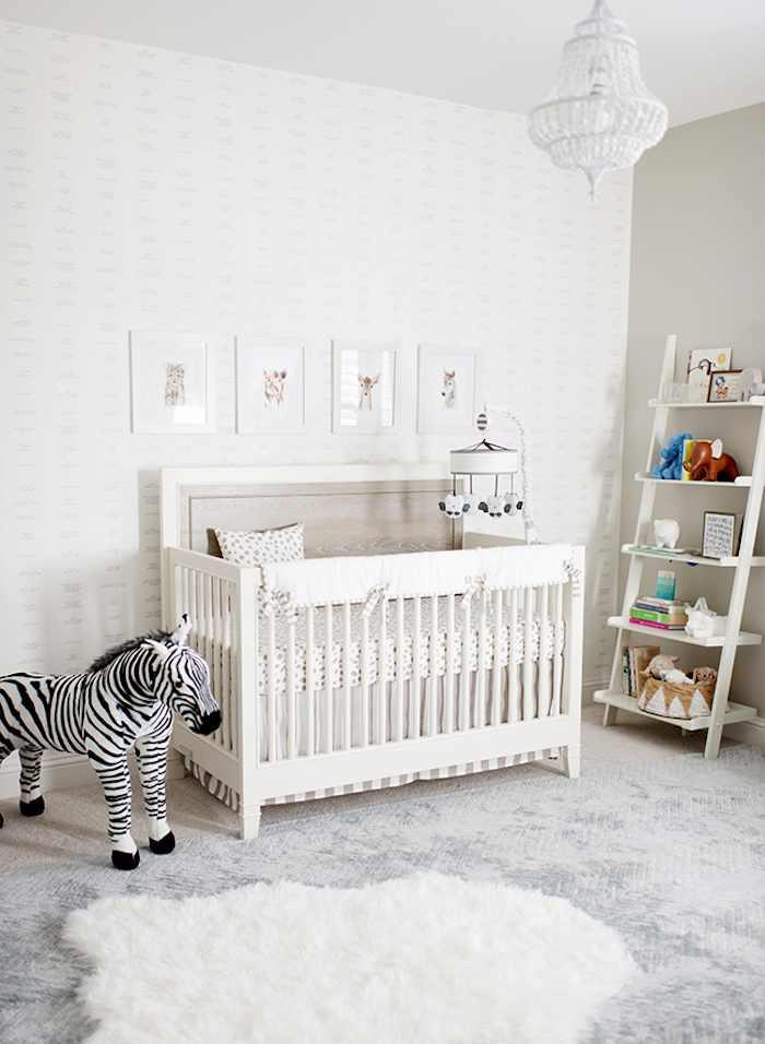 chandelier in white, inside baby room in light neutral colors, girl nursery themes, white crib near stuffed zebra toy, pale wallpaper and four framed drawings of animals