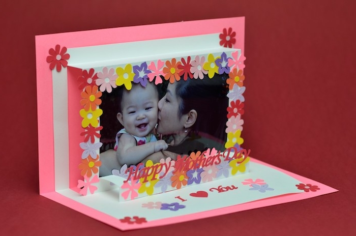 3D effect card, in neon pink and white, last minute mother's day gift ideas, decorated with small paper flowers, image of smiling baby, kissed by mom