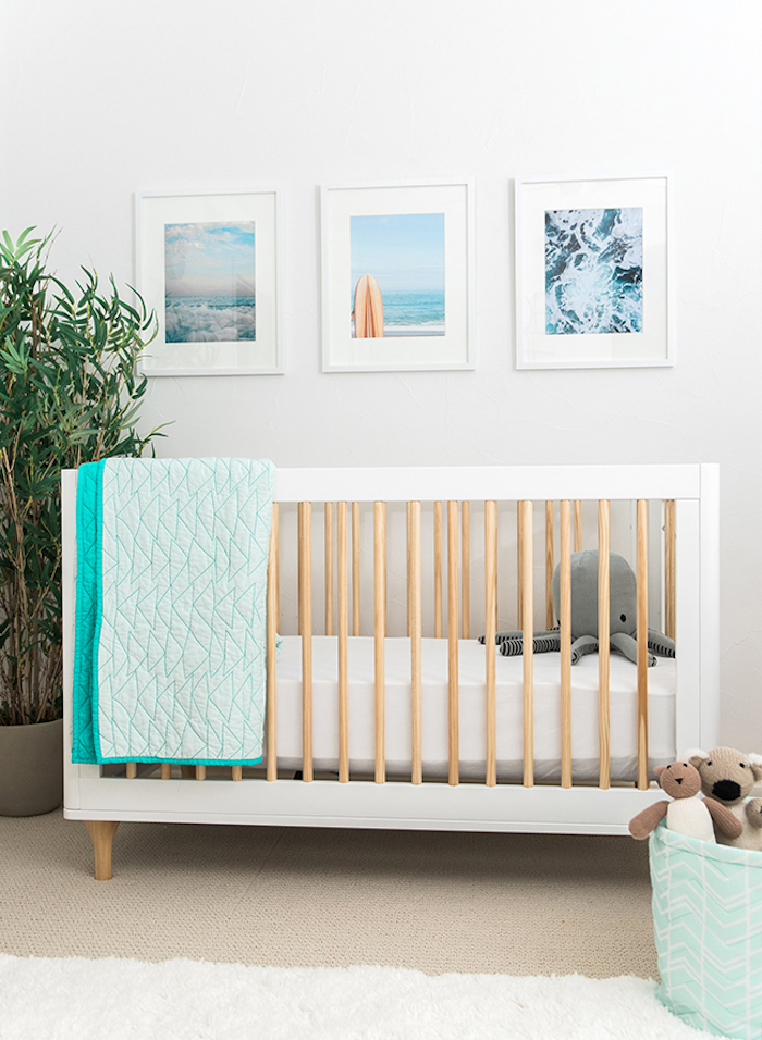 three images in white frames, hanging over white wooden crib, with beige details, gender neutral nursery, large green plant, stuffed gray octopus toy