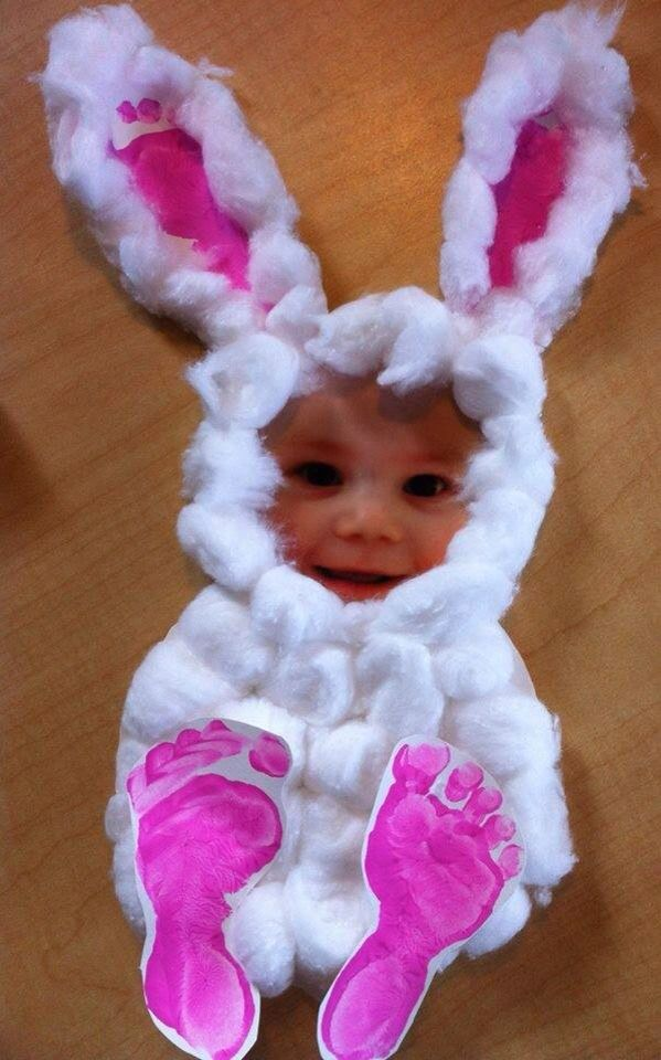 bunny-shaped paper figure, easter crafts for preschoolers, with white cotton balls, and decorated with child's footprints in pink, and a photo of a child's face