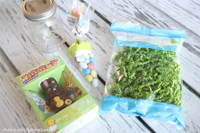 clear glass mason jar, near bag of green paper easter grass, easter projects, packet of small, egg-shaped candy, and a chocolate bunny