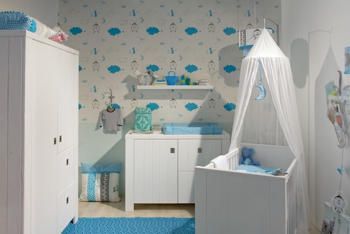 vivid blue and white room, baby boy nursery, white wooden crib, with matching wardrobe, and changing table, blue rug on light laminate floor
