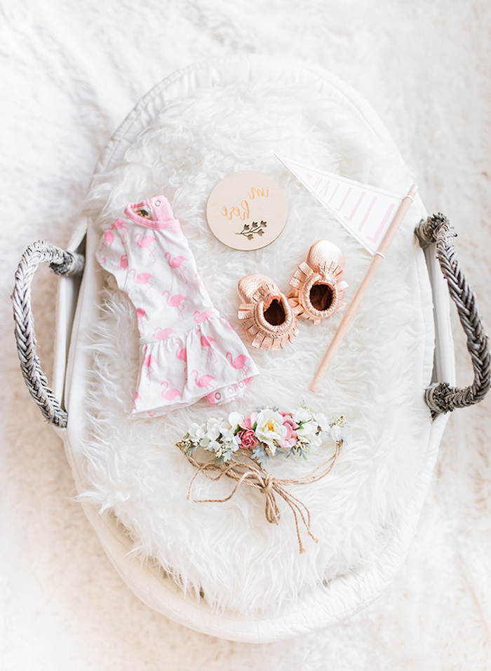 fluffy white carpet, baby girl nursery ideas, with pale gray basket, containing white plush cover, pale pink baby's dress, with flamingo pattern, tiny rose gold shoes, and others