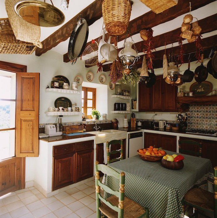 pans and baskets, and dried vegetables and herbs, hanging from the wooden beams of a ceiling, inside a room with rustic kitchen cabinets, small square table, with vintage green and beige chairs