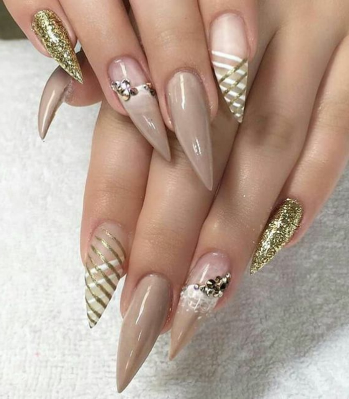 very long and sharp stilleto nail designs, painted in nude beige, and clear nail polish, decorated with golden glitter, stickers and hand-painted figures, in white and gold