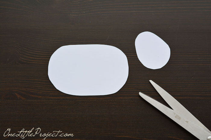 big oval and small, roundish white paper cutouts, easter crafts for kids, on a dark wooden surface, near pair of scissors