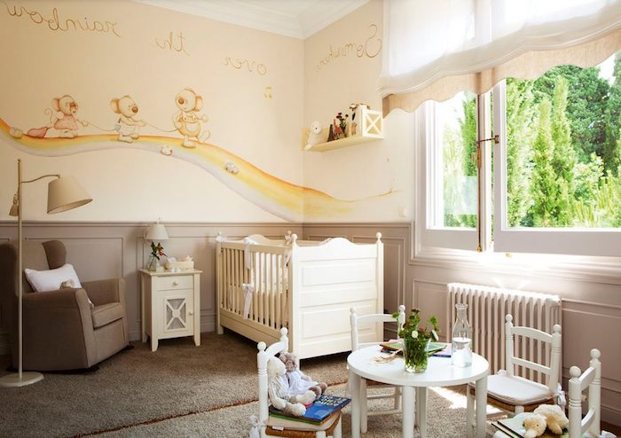beige carpets and armchair, in baby nursery, with yellow walls, decorated with light brown, yellow and blue mural, white wooden crib, small table and four chairs