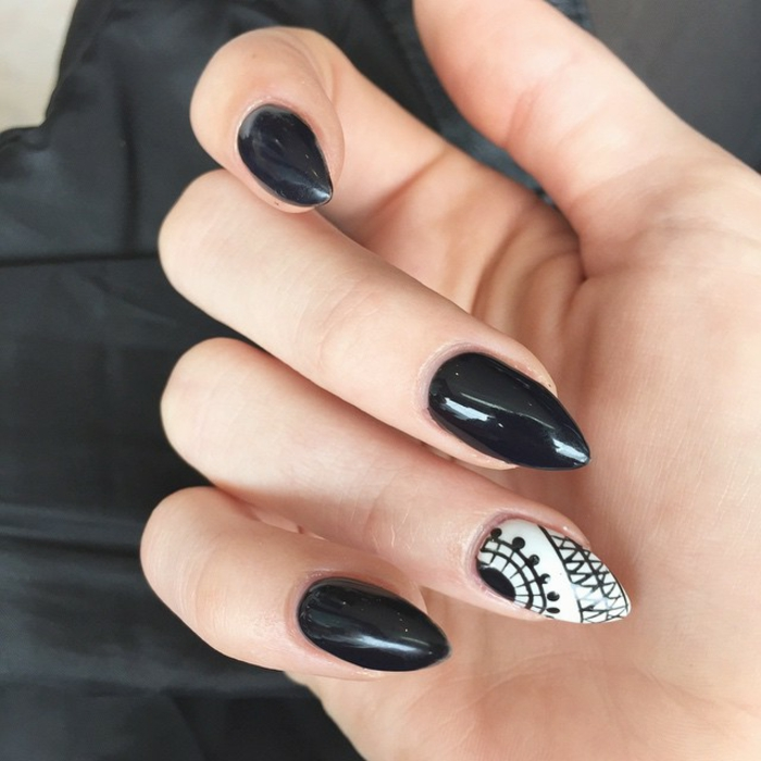 glossy and smooth, black and white nail polish, on sharp stiletto nails, with black hand-drawn decorations