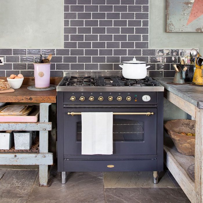 old fashioned black metal stove, in room with beige stone floor, pale gray walls, with dark gray brickwork details, shabby pale blue and brown, rustic kitchen cabinets