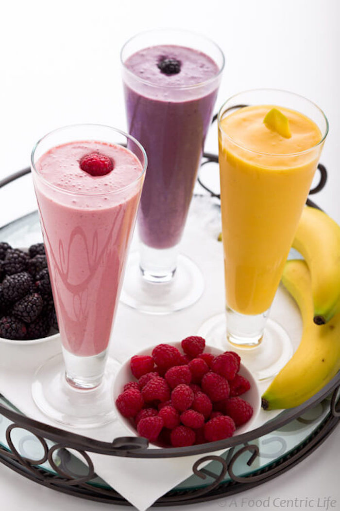 blackberries and strawberries in little white bowls, on tray containing two bananas, and three tall glasses, with blended drinks in different colors, smoothie recipes, each glass is topped with a different fruit