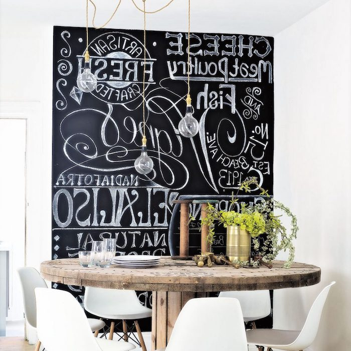 industrial wooden reel, transformed into a small dining table, with six white modern chairs, inside rustic kitchen, blackboard with white writing, covering the wall in the background