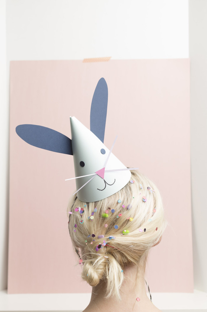 party paper hat, decorated with blue bunny ears, and a simple collaged face, on the head of a blonde woman, with tied hair, covered in colorful confetti and candy, cute crafts for adults and kids