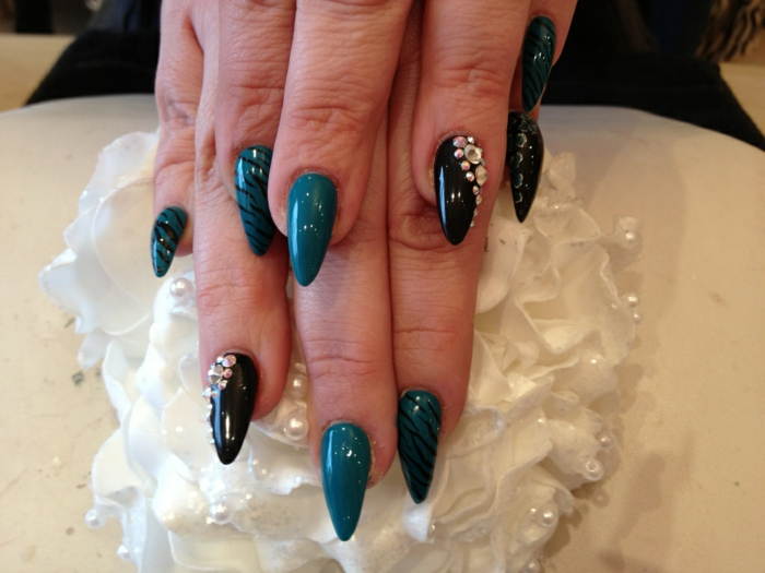 thin and long, pointy and sharp nails, decorated with iridescent rhinestone stickers, and black hand-drawn zebra pattern