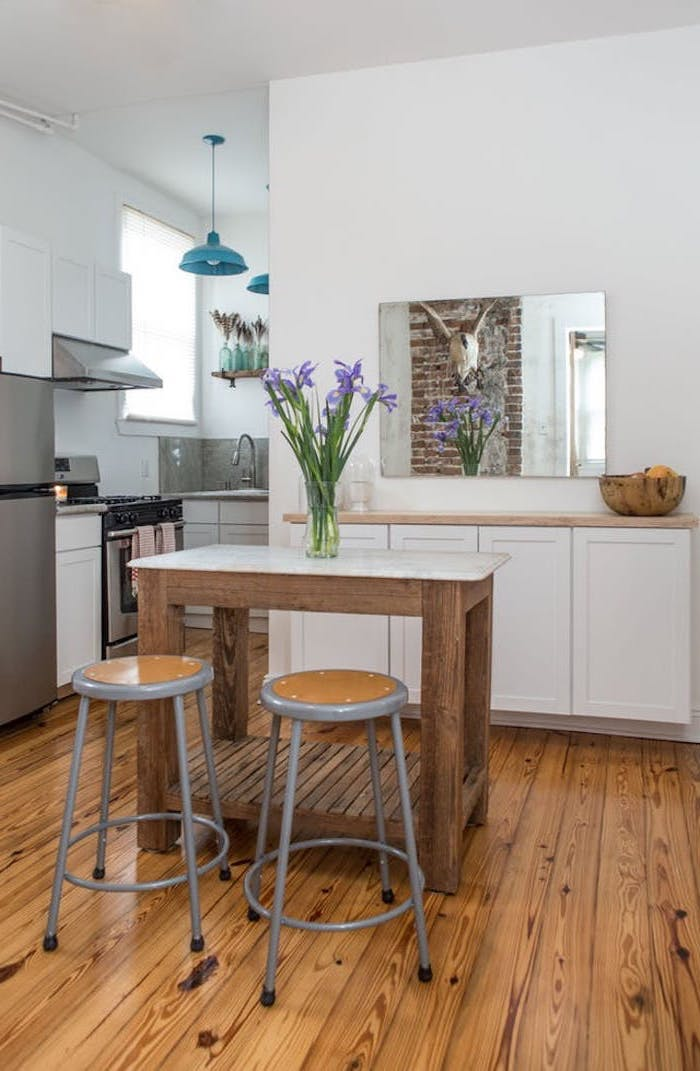 small wooden table, with flower vase, and two grey and brown stools, inside white kitchen, with light brown wooden floorboards, rustic home touches