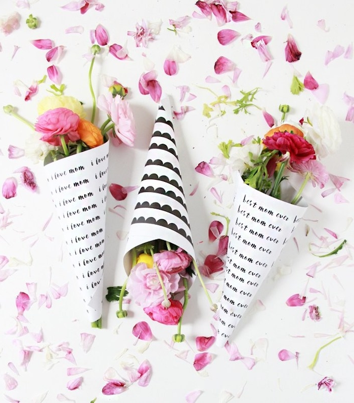 roses in light and dark pink, orange and yellow, wrapped in white paper, decorated with black customized print, top 10 mother's day gift ideas, pink petals in background