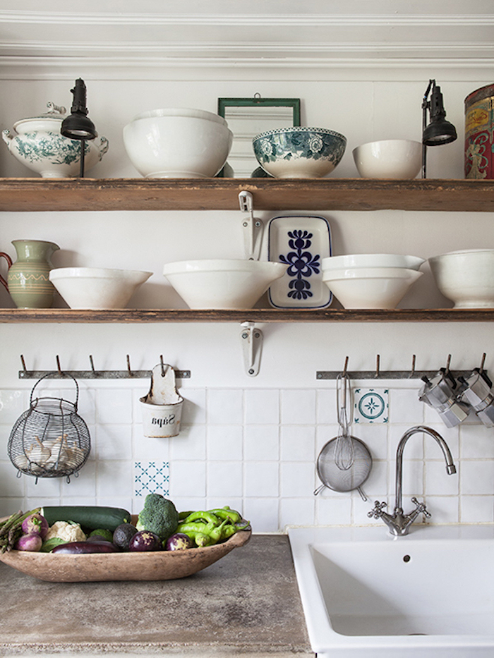 various white bowls, two lamps and a pale green pitcher, on two wooden shelves, above a vintage sink, inbuilt in a stone counter, vegetables in a large wooden dish