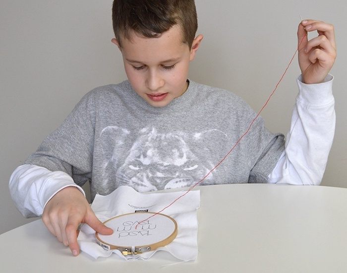 young boy embroidering, with red thread, on white piece of cloth, top 10 mother's day gift ideas, sweet message for mom