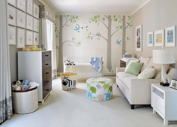 woodland wall decal, with threes and birds, in large baby nursery, with white crib and sofa, lots of framed drawings, chest of drawers and cupboard
