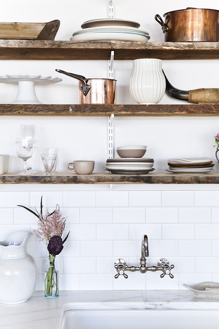 ceramic jugs and plates, and various brass pots, on wooden shelves, suspended over an antique sink, marble-like white and gray surface