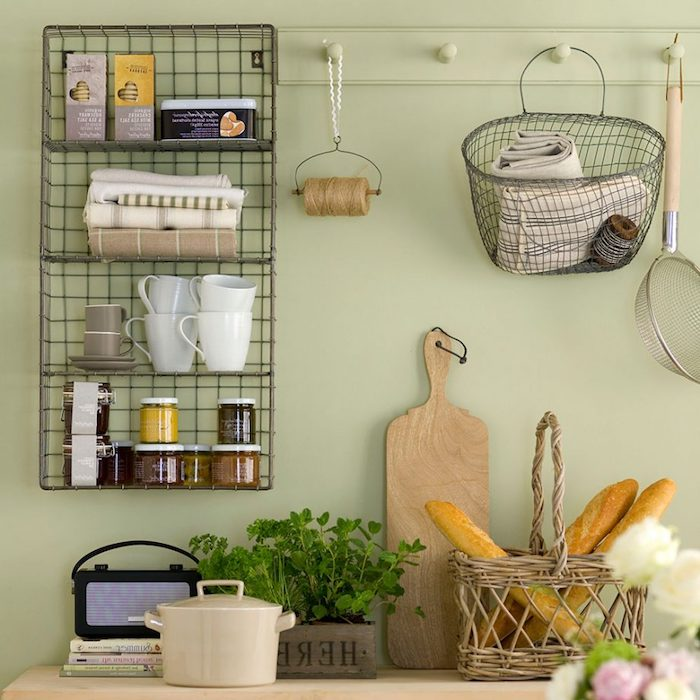 wire mesh shelves, covered with mugs, small jars and boxes of cookies, on pale pastel green wall, near counter with bread basket, planter with green herbs, and other rustic kitchen items