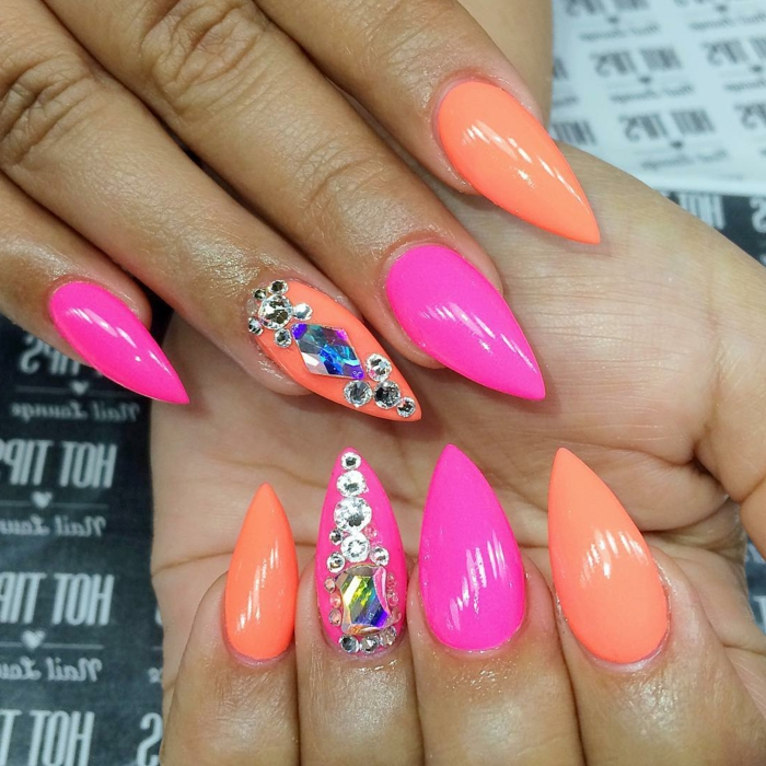 neon orange and pink nail polish, stilleto nail designs, decorated with silver and blue rhinestone stickers