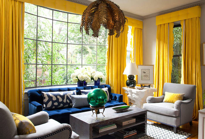 bright yellow curtains, in room with large windows, living room color ideas, navy sofa and light gray armchairs, massive wooden coffee table