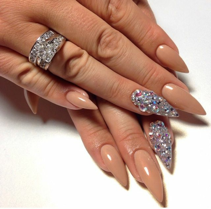 gem nail decal stickers, in many different colors, on manicure with nude beige nail polish, and long stiletto nails, on hand with encrusted silver ring