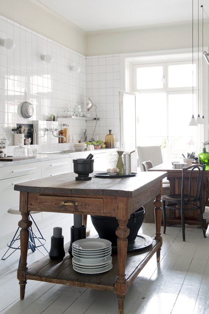 vintage wooden kitchen island, inside bright room, with white tiles on the walls, white cupboards and sink