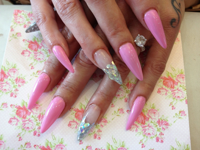 barbie pink manicure, decorated with silver, fish scale-like glitter, and clear nail polish, on long claw nails