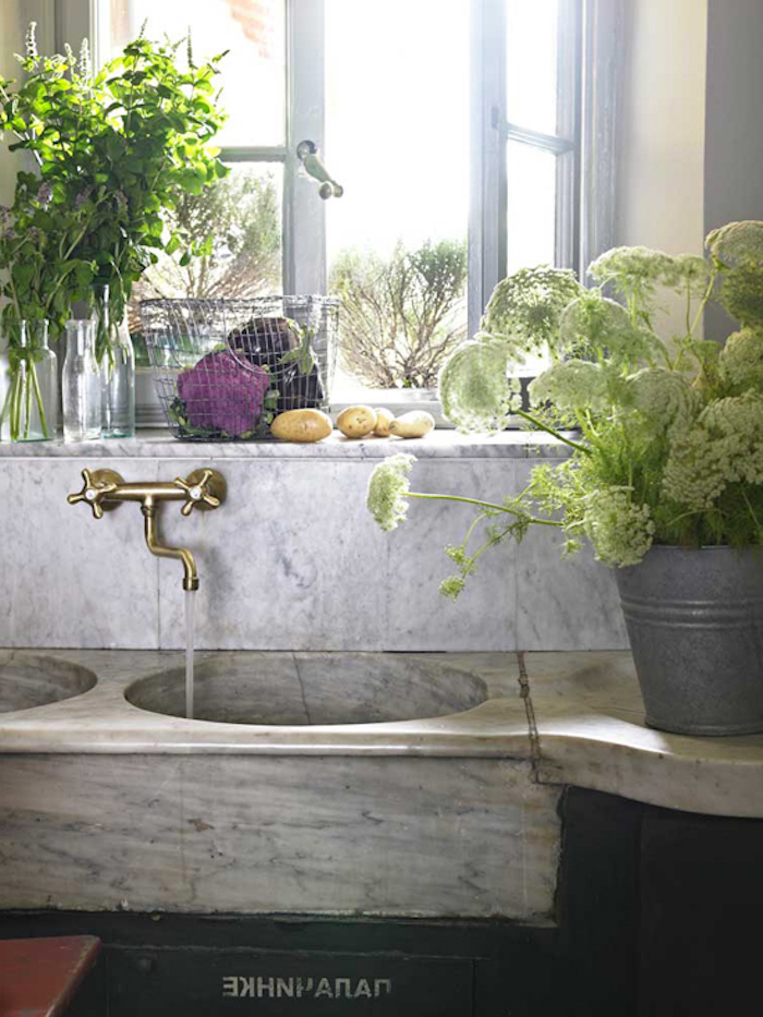open window next to a stone sink, with retro metal tap, a bucket with flowers, and vases with fresh herbs nearby